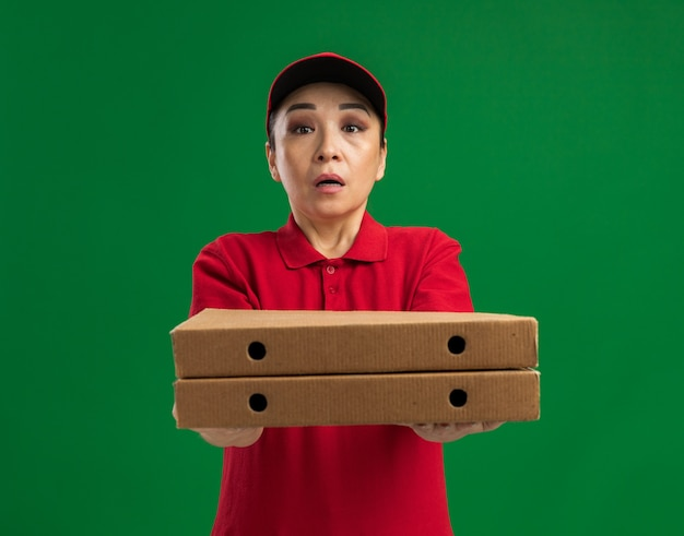 Jeune livreuse en uniforme rouge et casquette tenant des boîtes à pizza confondues