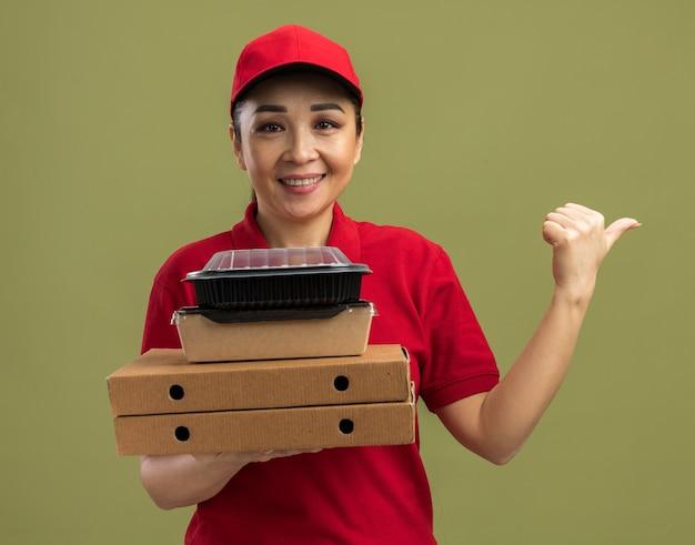 Jeune livreuse en uniforme rouge et casquette tenant des boîtes à pizza et des emballages alimentaires souriant amicalement pointant le doigt sur le côté debout sur un mur vert