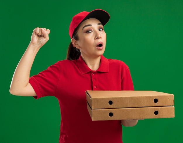 Jeune livreuse en uniforme rouge et casquette tenant des boîtes à pizza levant le poing étant surprise debout sur un mur vert