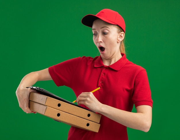 Jeune livreuse en uniforme rouge et casquette tenant des boîtes à pizza et un presse-papiers avec des pages blanches avec un crayon l'air surpris d'écrire quelque chose debout sur un mur vert