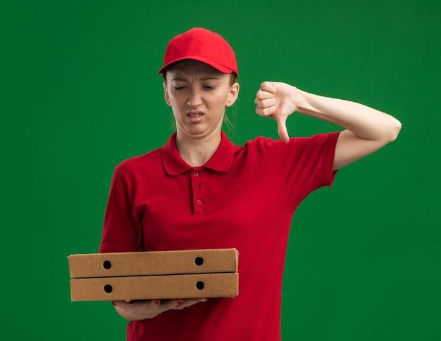 Jeune livreuse en uniforme rouge et casquette tenant des boîtes à pizza en les regardant mécontent montrant les pouces vers le bas debout sur le mur vert