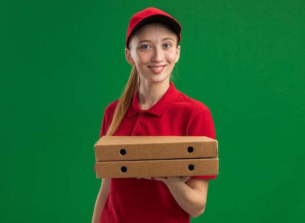 Jeune livreuse en uniforme rouge et casquette tenant des boîtes à pizza avec sourire sur un visage heureux debout sur un mur vert