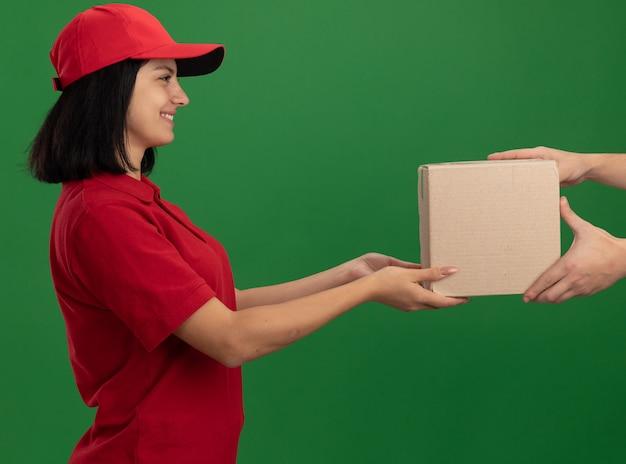 Jeune livreuse en uniforme rouge et chapeau donnant une boîte en carton à un client souriant debout sur un mur vert