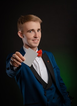 Le jeune magicien tient des cartes dans ses mains