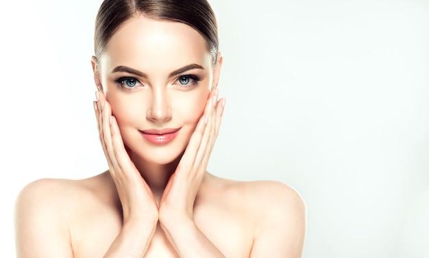 Jeune et magnifique mannequin touche doucement sa peau bien soignée des joues.