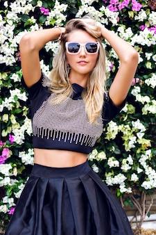 Jeune magnifique superbe jeune femme blonde, vêtue d'une tenue élégante, jupe midi, top court étincelant à la mode et lunettes de soleil, posant dans un jardin fleuri