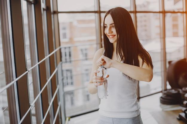Jeune et maigre fille dans une chemise blanche et des leggings gris, debout dans une salle de sport avec une bouteille