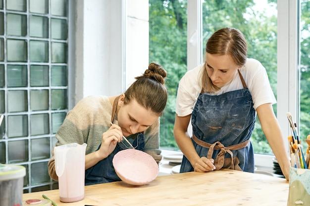 Jeune maître de poterie habile enseignant la sculpture et la peinture d'apprenti bol de boue