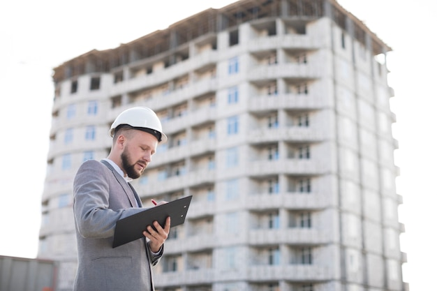 Jeune mâle architecture écrit sur le presse-papiers sur le chantier de construction