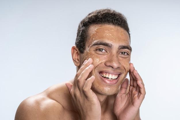 Jeune mâle gai répandant un masque facial sur ses joues