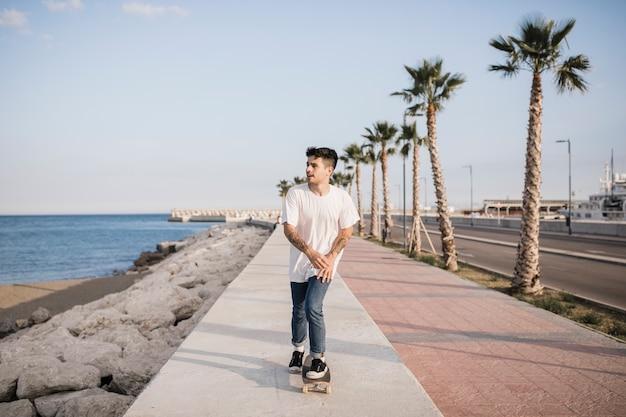 Jeune mâle patiner sur le trottoir avec planche à roulettes