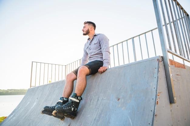Jeune mâle rollerskater assis dans le skate park