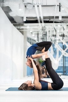Jeune maman adulte faisant du fitness avec sa petite fille