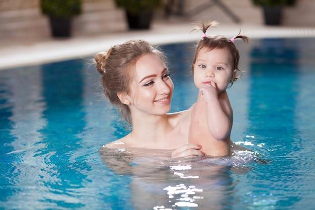 Jeune maman baigne le bébé dans la piscine.
