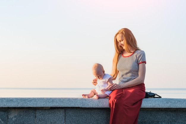 Jeune maman et bébé au coucher du soleil sur fond de mer. concept de maternité heureuse.