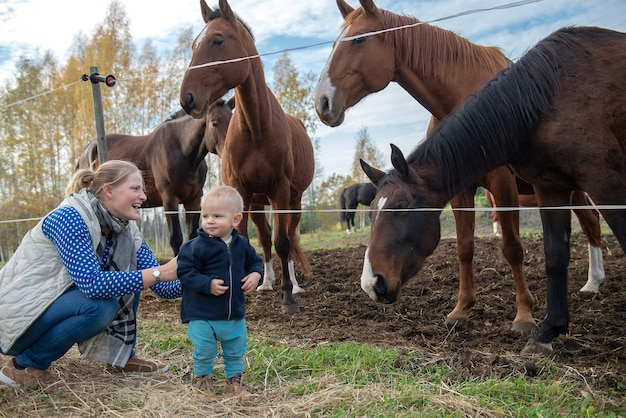 Jeune maman et bébé passent un bon moment au paddock de chevaux dans un environnement de campagne