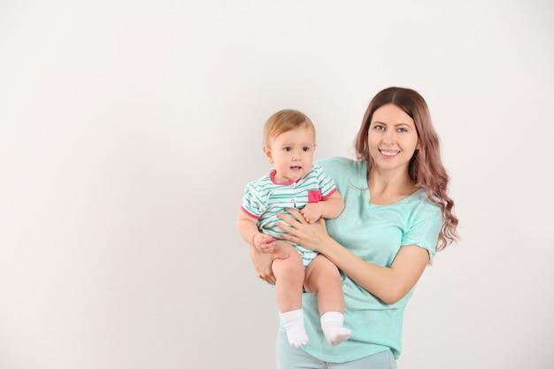 Jeune maman avec bébé sur une surface blanche