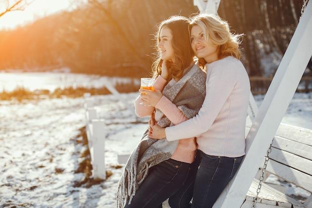 Jeune maman blonde avec sa fille adulte dans le parc du printemps