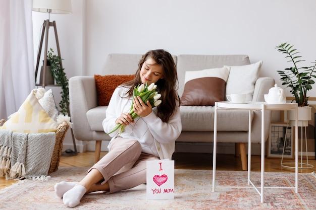 Jeune maman avec un bouquet de fleurs dans le salon en vacances
