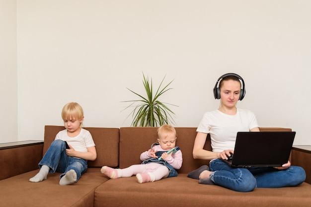 Jeune maman et deux enfants assis sur un canapé avec ordinateur et téléphone. dépendance aux personnes et à la technologie