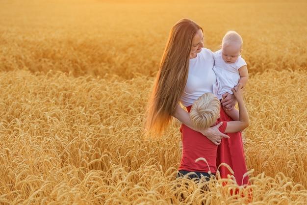 Jeune maman avec deux enfants au milieu du champ de blé. famille heureuse.