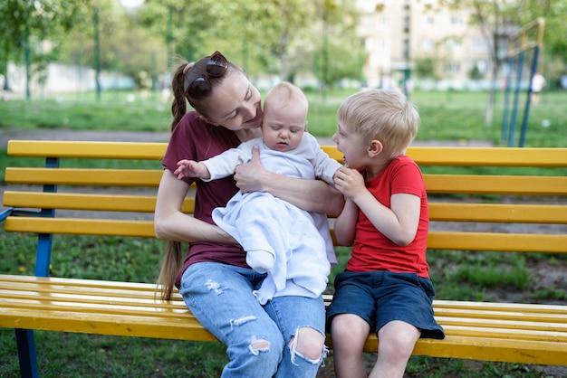 Jeune maman et deux enfants sur un banc dans le parc.