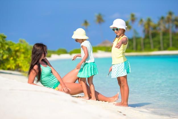 Jeune maman et deux ses petites filles sur une plage exotique aux beaux jours