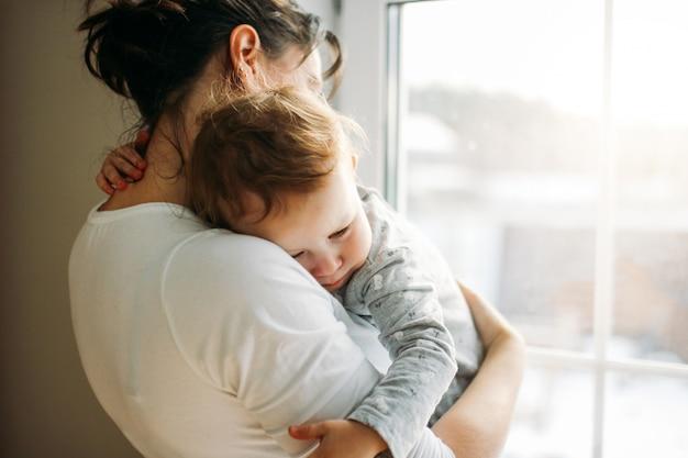 Jeune maman, à, dorlotez fille, sur, mains, près, fenêtre, chez soi