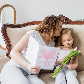 Jeune maman embrassant sa fille tenant la carte de voeux pour la fête des mères