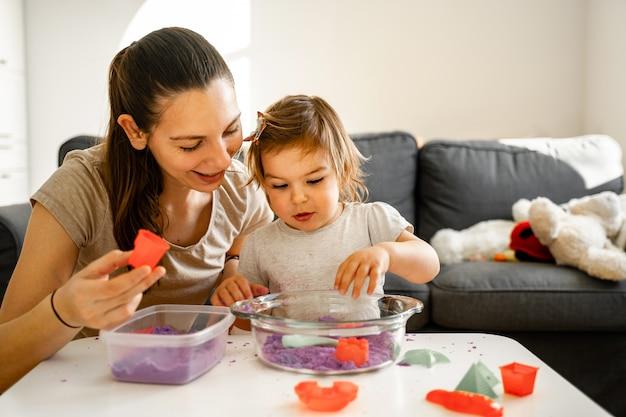 Jeune maman avec enfant jouant du sable cinétique. bon temps de liaison ensemble. développement de la créativité
