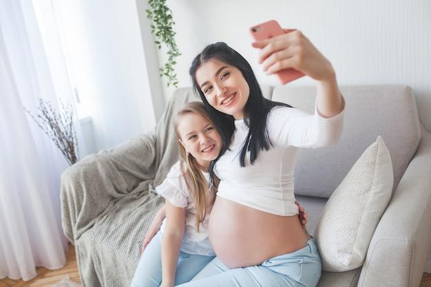 Jeune maman faisant selfie avec sa petite fille. femme attend bébé. famille heureuse à l'intérieur.