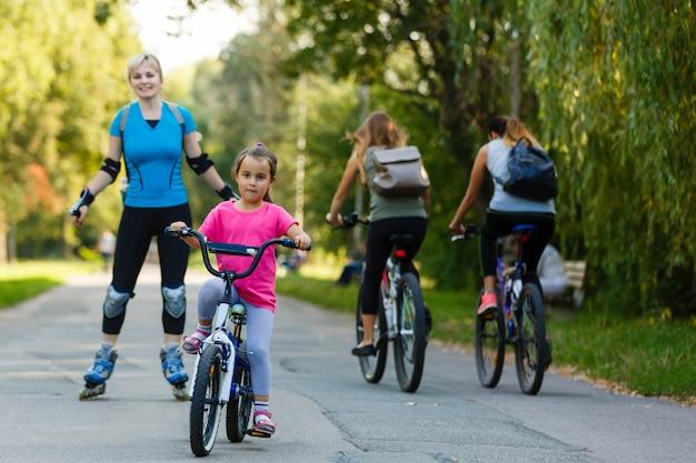 Une jeune maman fait du roller. fille faire du vélo