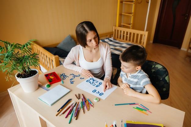 Une jeune maman fait ses devoirs avec elle. parents et formation.