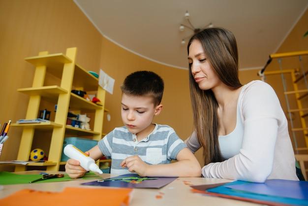 Jeune maman fait ses devoirs avec son fils à la maison. parents et formation