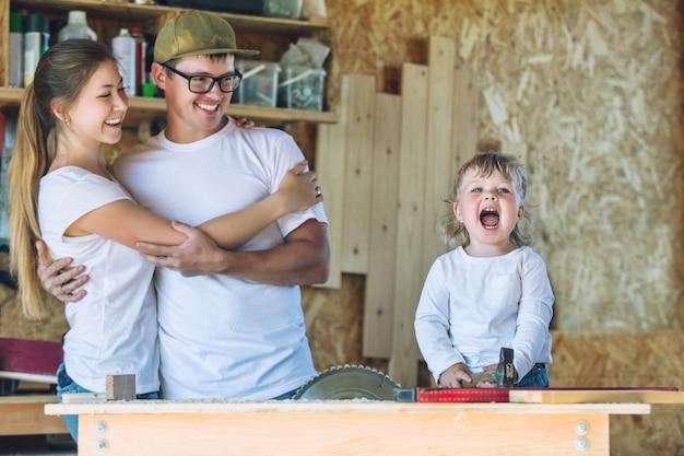 Jeune maman de famille heureuse, papa et bébé dans l'atelier de menuiserie travaillant avec des outils