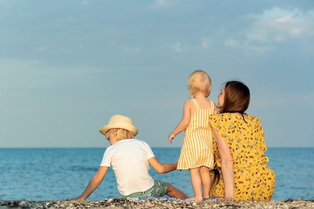 Jeune maman avec fille et fils se reposent sur le bord de la mer. vacances en famille au bord de la mer.