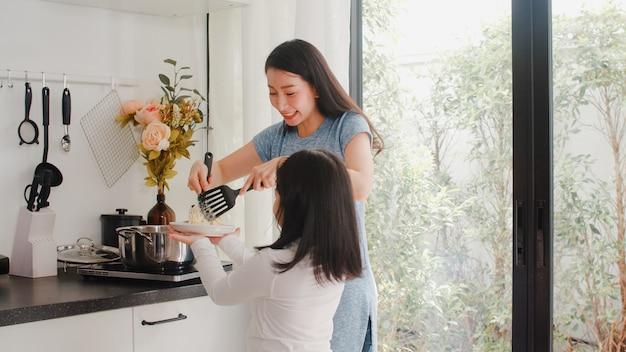 Jeune maman et fille japonaise asiatiques cuisinant à la maison. femmes de style de vie heureux faire des pâtes et des spaghettis ensemble pour le petit déjeuner dans la cuisine moderne à la maison le matin.