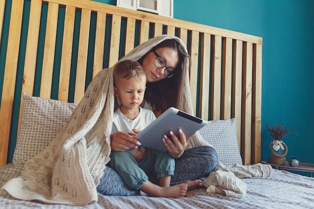 Jeune maman et fils avec une tablette sous une couverture confortable dans la chambre