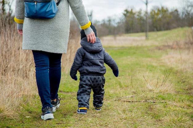 Jeune maman avec garçon d'enfant en bas âge à l'extérieur.