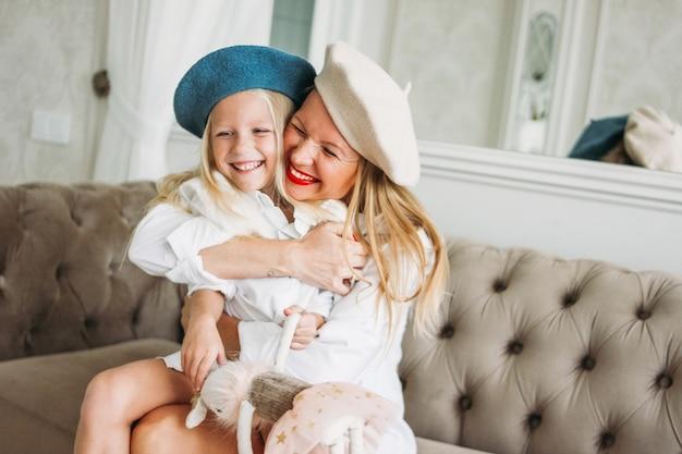 Jeune maman heureuse cheveux blonds juste heureux et sa jolie fille s'amuser ensemble au salon, mode de vie familial heureux