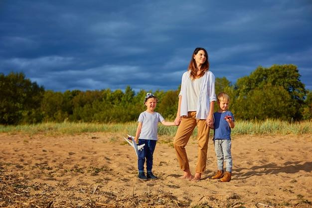 Une jeune maman heureuse avec deux garçons jouant sur le sable près de la forêt, dans les mains de l'un d'eux une maquette d'avion civil et un chapeau sur la tête