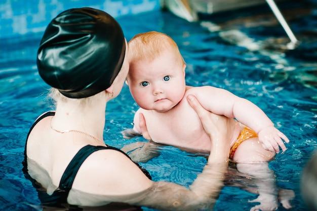 Jeune maman, instructeur de natation et heureuse petite fille dans la pataugeoire. apprend à l'enfant à nager. profitez de la première journée de baignade dans l'eau. maman tient la main de l'enfant se préparant à la plongée. faire des exercices