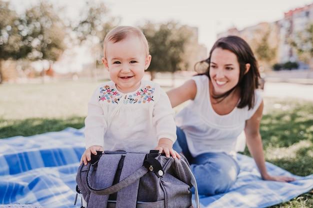 Jeune maman jouant avec bébé fille à l'extérieur dans un parc, concept de famille heureuse. amour mère fille