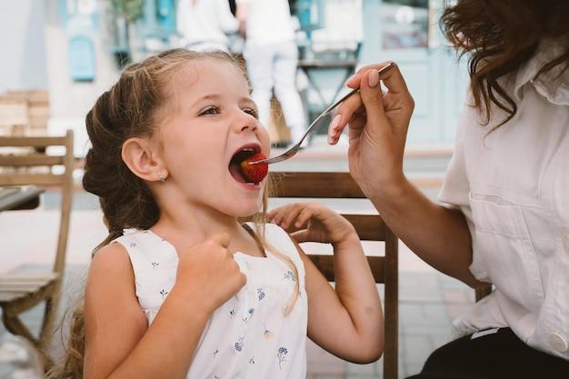 Jeune maman mangeant un gâteau avec un enfant souriant dans la rue