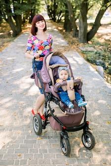 Jeune maman marche avec bébé souriant dans une poussette marron. parents marchant à l'extérieur avec un enfant dans la poussette d'été.