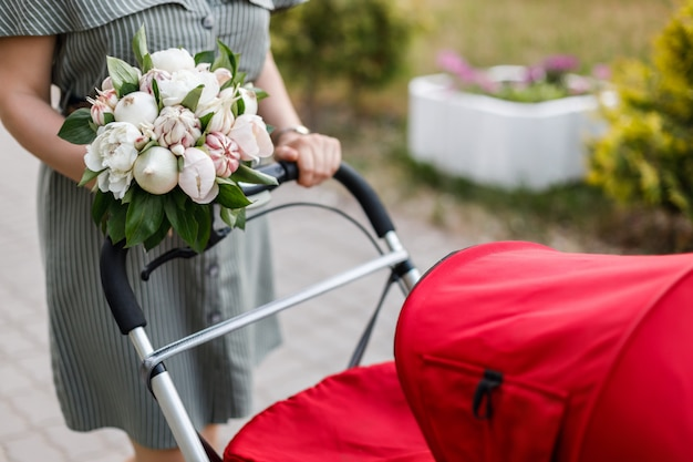 Jeune maman marche avec une poussette rouge et tient dans ses mains un bouquet original de fleurs, d'oignons et d'ail