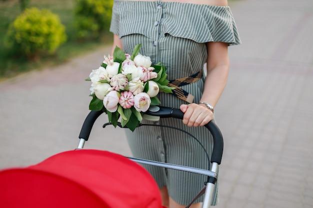Jeune maman marche avec une poussette rouge et tient dans ses mains un bouquet original de fleurs, oignons et ail