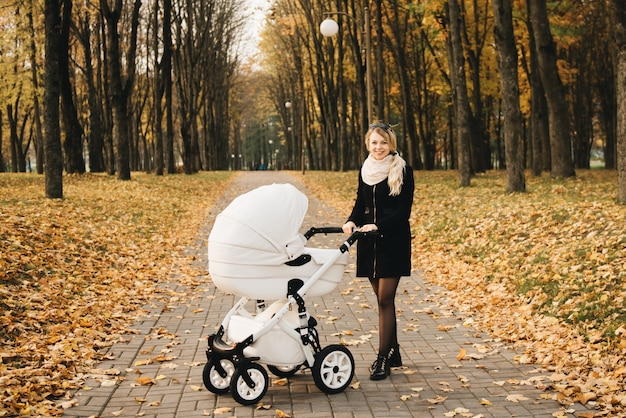 Une jeune maman marche avec son bébé dans le parc en automne. maman avec poussette blanche