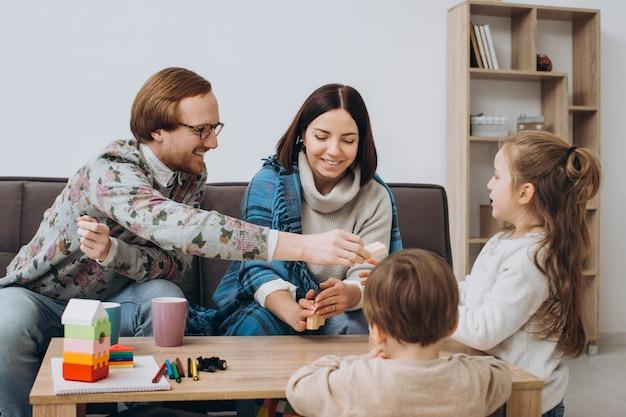Jeune maman et papa jouent à des jeux éducatifs avec les enfants