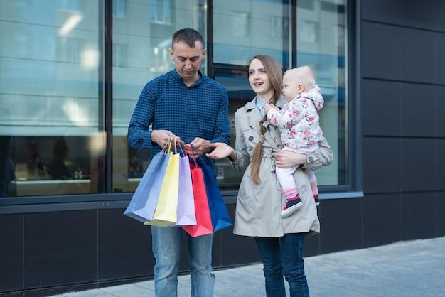 Jeune maman avec petite fille sur les bras. père avec des sacs à main. shopping en famille. centre commercial